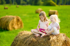 Twio little sisters sitting on a haystack Stock Photo
