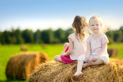 Twio little sisters sitting on a haystack Stock Photos