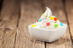 Twirled vanilla ice cream with colorful candy Royalty Free Stock Photo