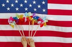 Twirlers coloridos do vento na frente da bandeira dos EUA Fotografia de Stock