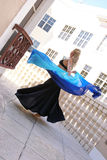 Twirling belly dancer. Beautiful blonde belly dancer spinning around with veil on balcony outside buildings Royalty Free Stock Photos