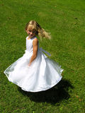 Twirling flower girl. A young girl twirls around in her flower girl dress Stock Photo