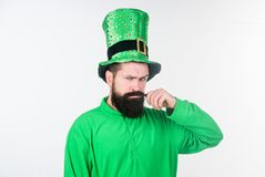 Twirling his moustache. Happy saint patricks day. Bearded man celebrating saint patricks day. Hipster in leprechaun hat. And costume. Irish man with beard royalty free stock photography