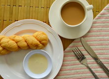 Twist bread dipping with sweetened condensed milk and coffee cup Royalty Free Stock Image