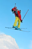 Twist and jump. A brightly dressed skier takes off and twists his body Royalty Free Stock Photography