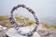 Twisted. White spiral of pebbles on the boulder at the sea royalty free stock image