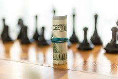 Twisted american dollars on chessboard against black pieces Royalty Free Stock Photos