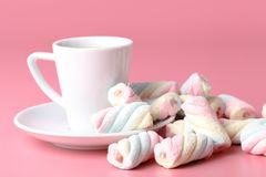Twisted american marshmallow on pink background with coffee cup Royalty Free Stock Photos