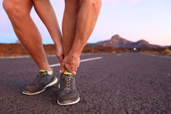Twisted angle - runner man with injury. Twisted angle - running sport injury. Male athlete runner touching foot in pain due to sprained ankle Royalty Free Stock Photo