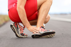 Twisted ankle. Broken twisted ankle - running sport injury. Male runner touching foot in pain due to sprained ankle Stock Image