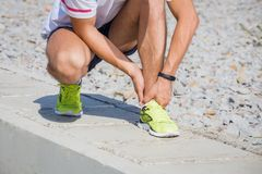 Twisted ankle while jogging. Running athlete feeling pain after having his leg injured. Accident on running track during the morning exercise. Sport accident royalty free stock photos