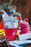 Twisted bills of dollars in red christmas bucket, euro and pink macaroons. New year`s gifts Stock Photo