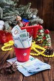Twisted bills of dollars in red christmas bucket, euro and pink macaroons. New year`s gifts Stock Photography