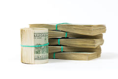 A twisted bundle of 100 dollar bills stands on packs of dollars. Royalty Free Stock Image