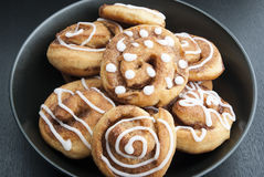 Twisted buns with cinnamon and icing sugar on a black background Stock Photos
