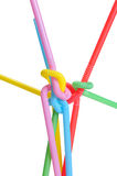 Twisted colored straws. Several drinking straws knotted togheter with different collors: red, green, pink, blue, yellow. Isolated on white Royalty Free Stock Photography