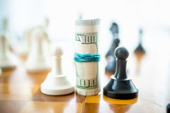 Twisted dollar bills standing on chess board between white and b Stock Photo