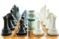 Twisted dollar bills between white and black chess pieces Royalty Free Stock Image