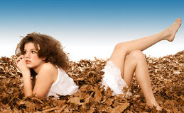 Twisted Fall. Beautiful teen girl laying in leaves with legs on backwards royalty free stock images