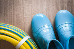 Twisted garden hose and waterproof gumboots on. Wooden board gardening concept stock photography