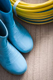Twisted garden hose and waterproof rubber boots on. Wooden surface gardening concept stock photos