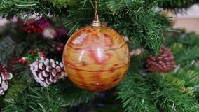 Twisted globe earth ball on Christmas tree. Decorated branch of a christmas tree with light background. 2015 2016 new year stock footage