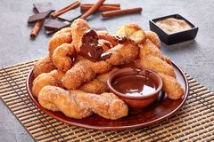 Twisted Korean doughnuts - Kkwabaegi on a plate. Twisted Korean doughnuts - Kkwabaegi sprinkled with sugar and served with chocolate sauce on a clay plate, on a royalty free stock photography