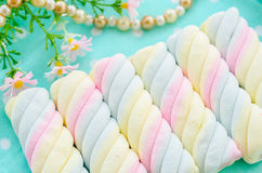 Twisted marshmallow with flower. Royalty Free Stock Photo