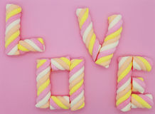 Twisted marshmallows on the pink background. Colorful twisted marshmallows on the pink background. Added together in world - LOVE Royalty Free Stock Photo