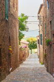 Twisted medieval streets with colorful flowers in Tuscany Royalty Free Stock Images