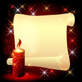 Twisted parchment and a burning candle Stock Photo