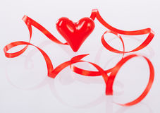 Twisted red ribbon and ceramic heart Stock Photo