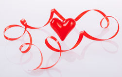 Twisted red ribbon and ceramic heart Royalty Free Stock Image