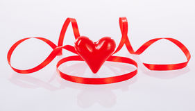 Twisted red ribbon and ceramic heart Stock Image