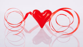 Twisted red ribbon and ceramic heart Stock Photography