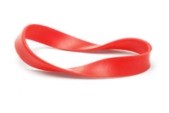 Twisted red rubber wrist band. On white background royalty free stock image