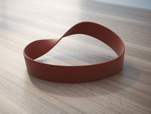 Twisted red rubber wrist band. On wooden table royalty free stock photo