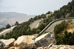 Twisted Road. In mountains. Seashore in the background. Blurred rocks in the foreground Stock Images