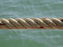 Twisted rope, against a background of the sea. Close up landscape image showing detail Stock Photos