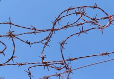 Twisted strands of barbed wire on sky background Royalty Free Stock Image