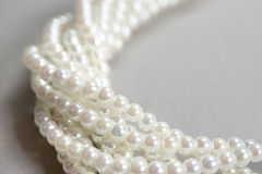 Twisted strands of white pearls. On a gray background Stock Photo