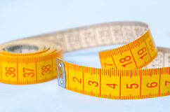 Twisted tape measure on blue background Stock Photo