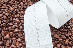Twisted type of electrocardiogram with printed ECG line lies on fried coffee beans. Impact coffee and caffeine on heart and heart royalty free stock photo