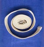 Twisted yoga iyengar white belt. Blue background Stock Image