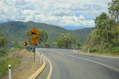 Twisting asphalt road in mountain. Yellow road signs attention dangerous turn, serpentine.  Stock Image