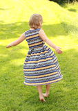 Twisting girl. Little barefoot girl twisting on meadow Royalty Free Stock Photos