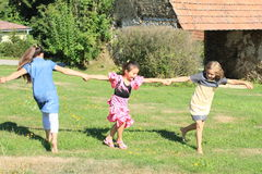 Twisting kids. Three happy little girls in dresses twisting and dancing around on green meadow Stock Photo
