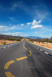Twisting lane marking on road in desert Royalty Free Stock Photo