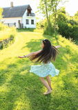 Twisting little girl. Twisting barefoot girl with flying long brunette hair dressed in green dress dancing on grass in front of a house Royalty Free Stock Photography