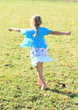 Twisting little girl. Twisting barefoot kid - girl with long blond braid in dress with blue and lila flowers and blue t-shirt dancing on green meadow Royalty Free Stock Photo